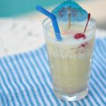 pina colada in tall glass with umbrella and cherry