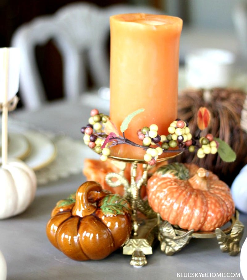 traditional autumn tablescape with orange candle and pumpkins