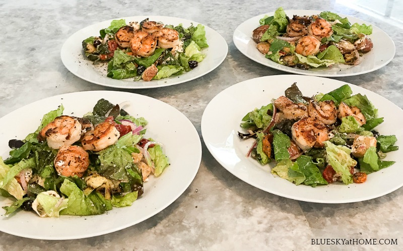 4 green salads with shrimp on white plates