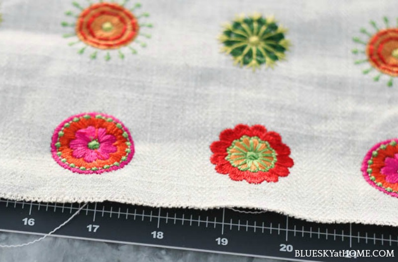 zipper and pink, green, orange embroidery circles on cream background
