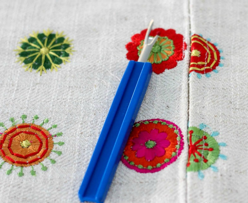 blue seam ripper on pink, green, orange embroidery circles on cream background