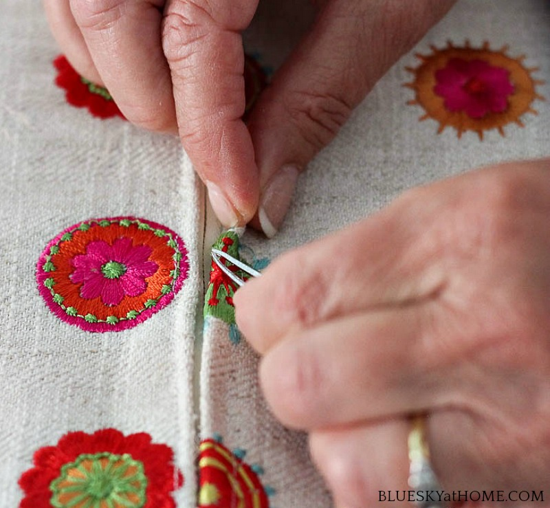 hands removing threads form fabric