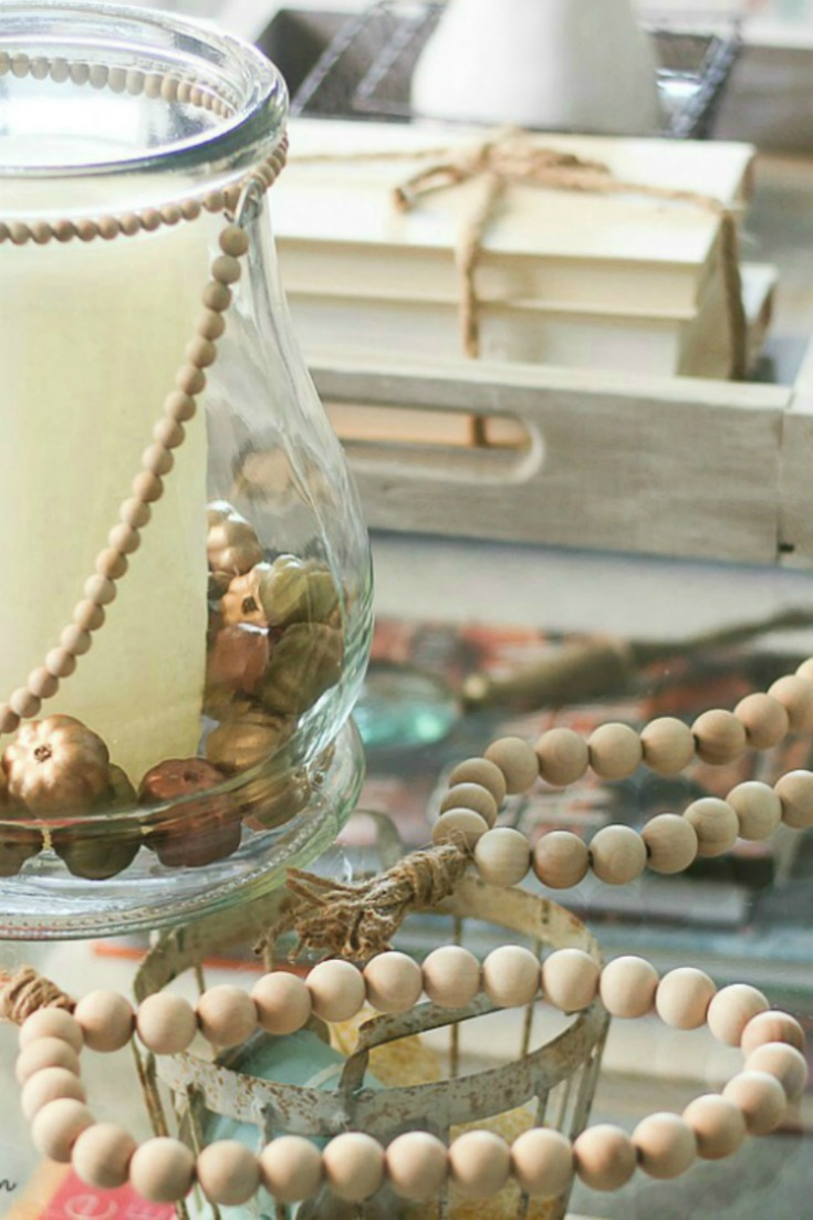 wooden beads and pumpkins in glass vase