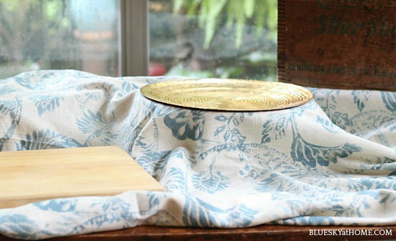 blue cloth on table with gold platter and wood cutting board