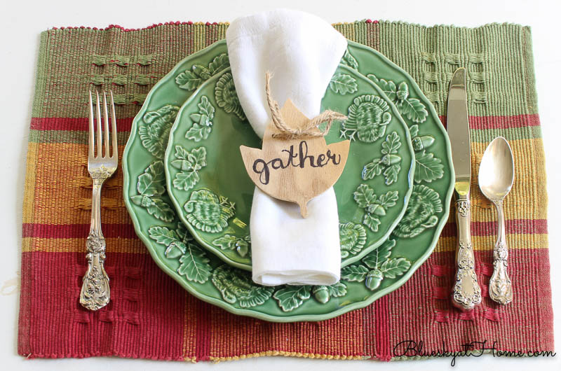 fall place setting with gather napkin ring on green plate