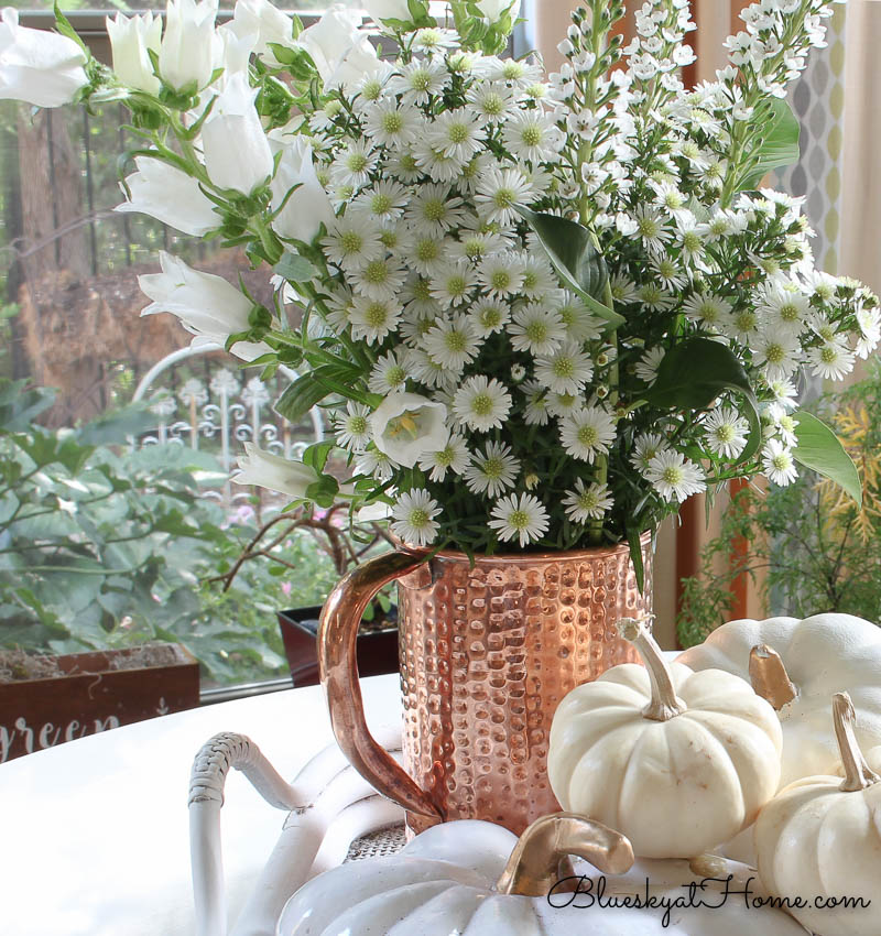 copper vase with white flowers and pumpkins