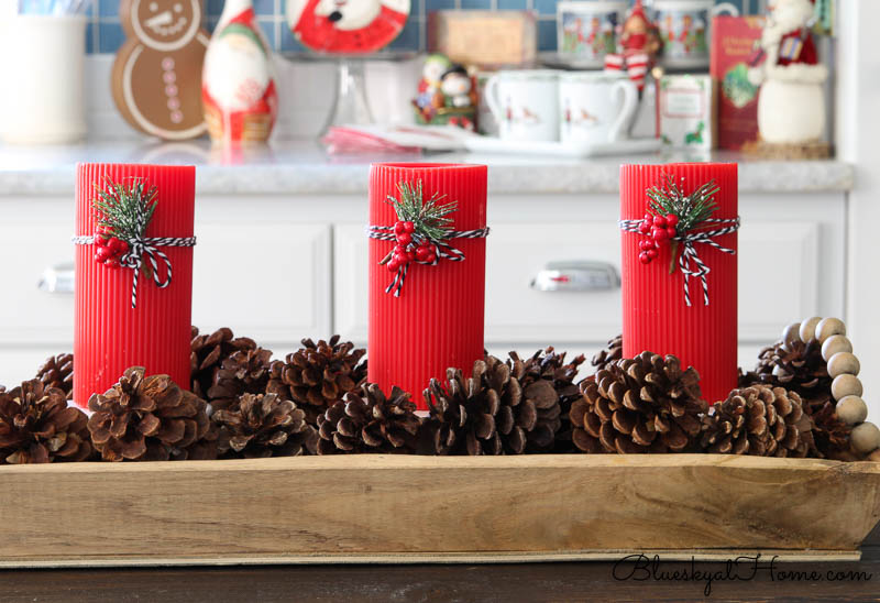 red Christmas candles in tray with pinecones