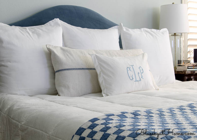 blue and white checked blanket on bed with pillows
