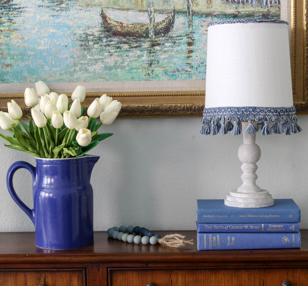 blue pitcher with white tulips and lamp