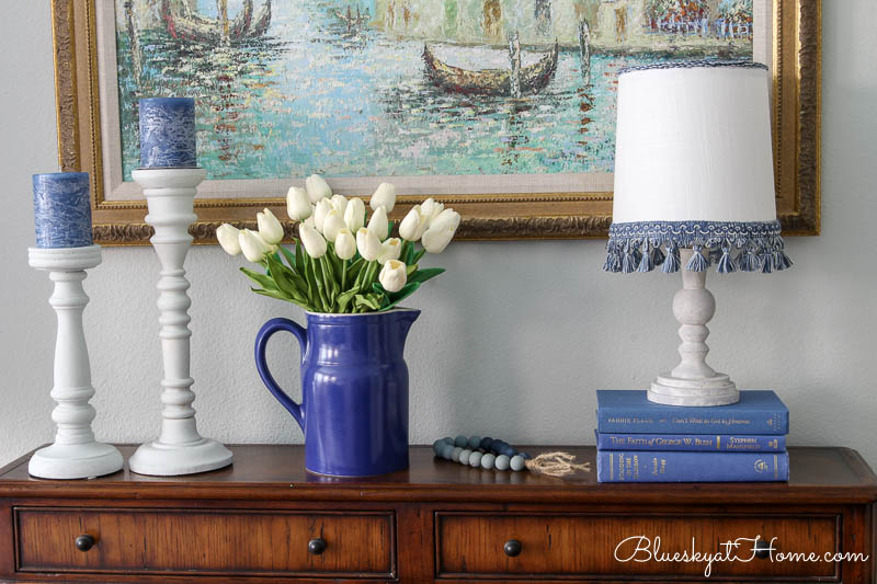 blue pitcher with white tulips and lamp and candlesticks in winter master bedroom