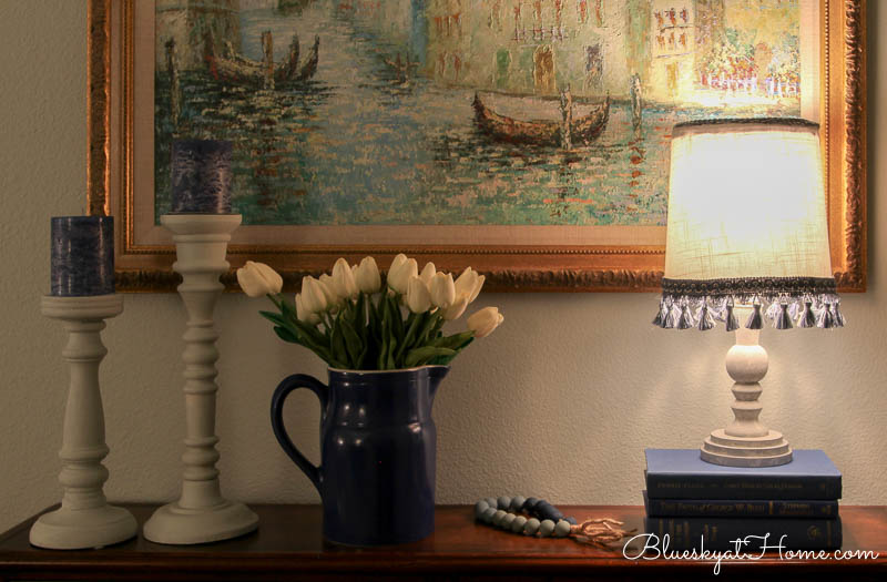 lamp at night with blue pitcher and white tulips