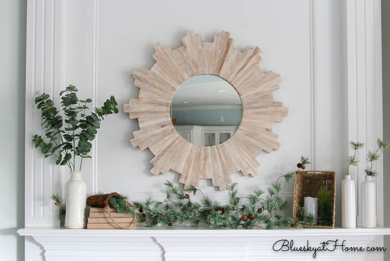 sunburst mirror above mantle with greenery