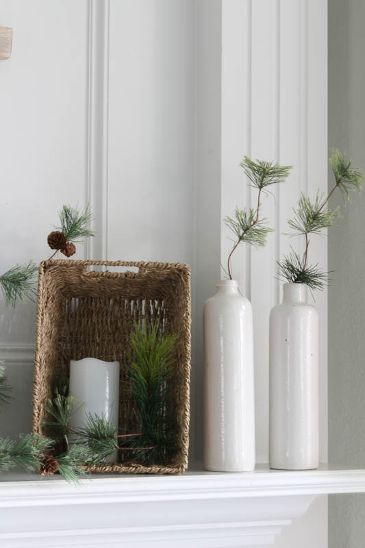white vases with greenery