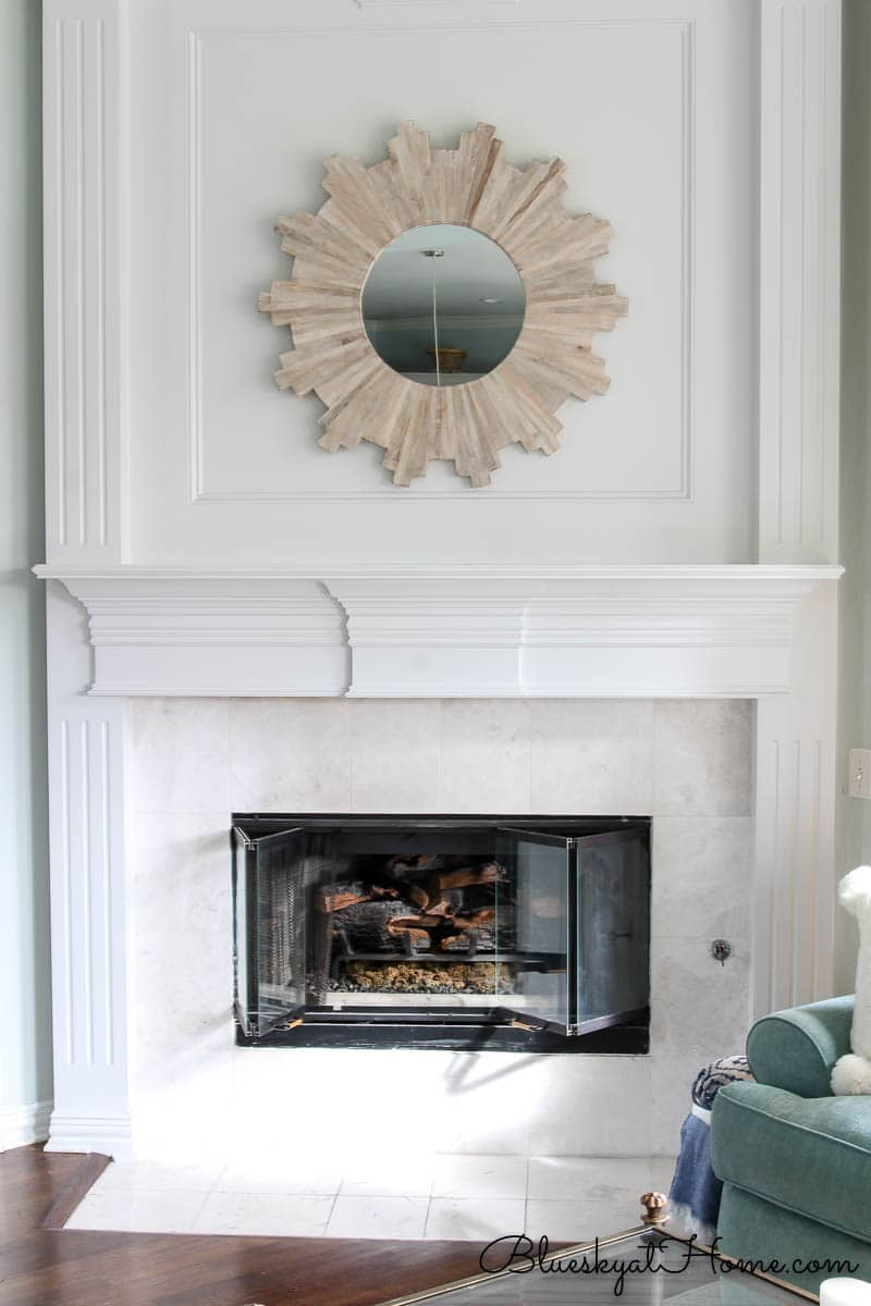 white mantle with wood sunburst mirror
