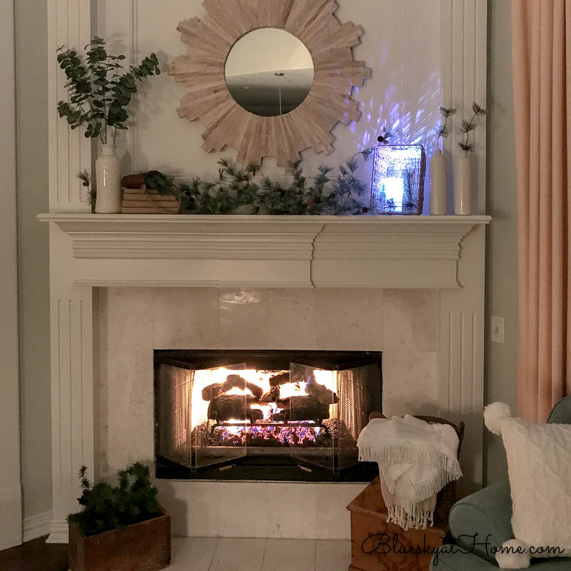 fireplace lit with winter decor