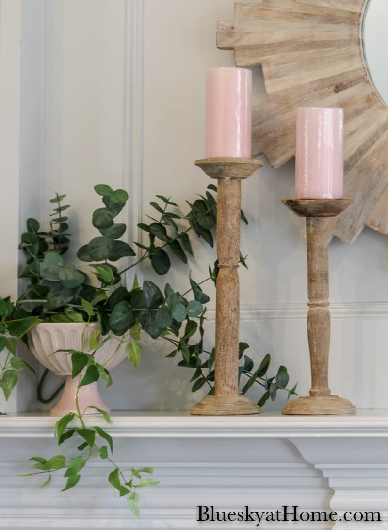 pink candles on wood cantlesticks