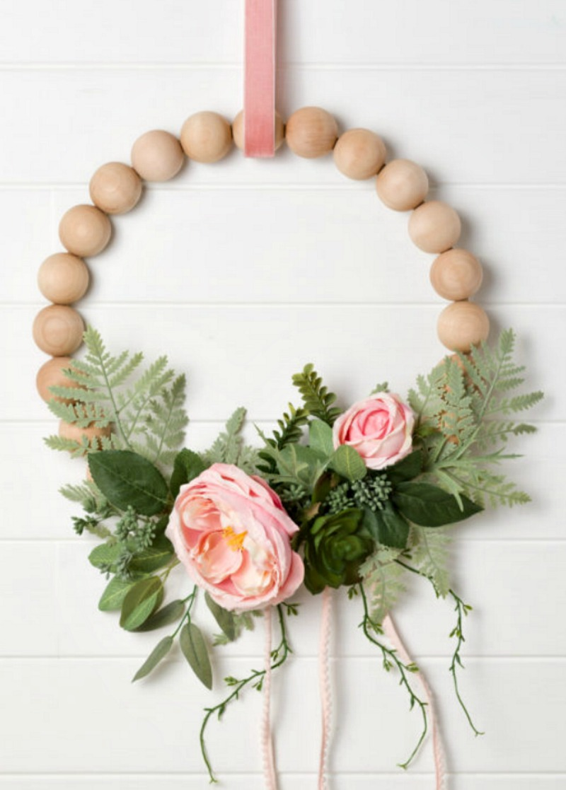 wood wreath with greenery and pink flowers