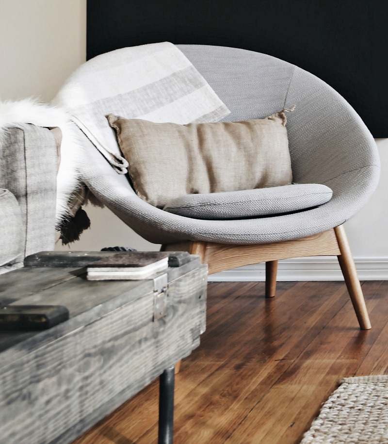 grey chair with pillow and blanket