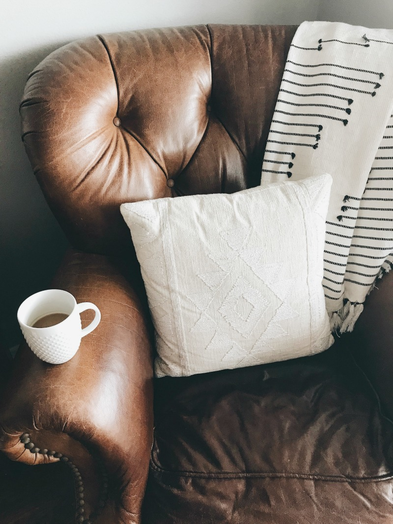 pillows and blanket on brown leather chair