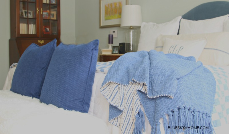 blue blanket, blue pillows on fur throw on bench