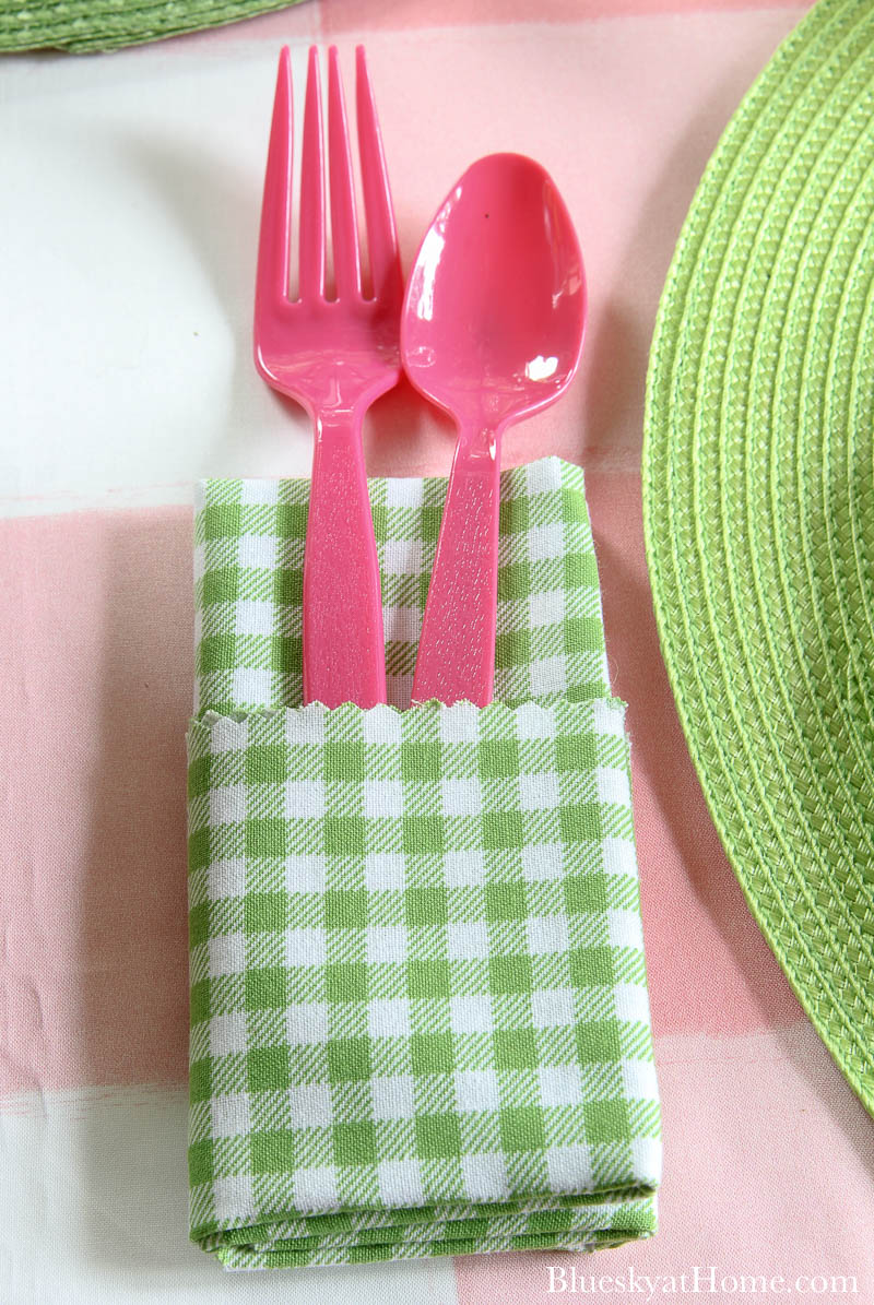 green adn white checked napkin with pink fork and spoon