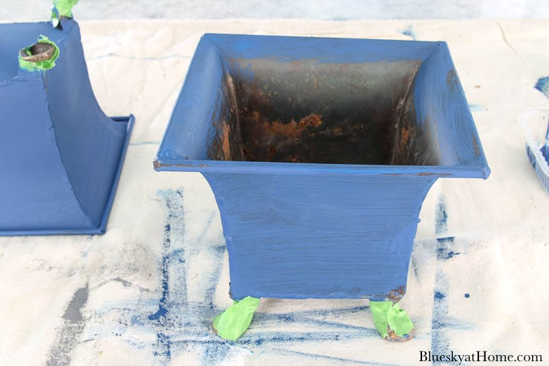 painting discarded containers blue