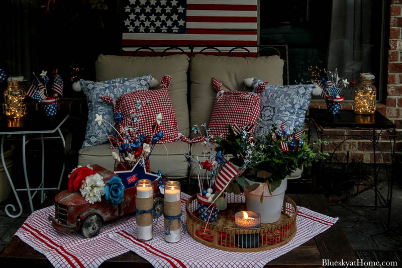 patio loveseat with red and bue pillows and 4th of July decorations at night