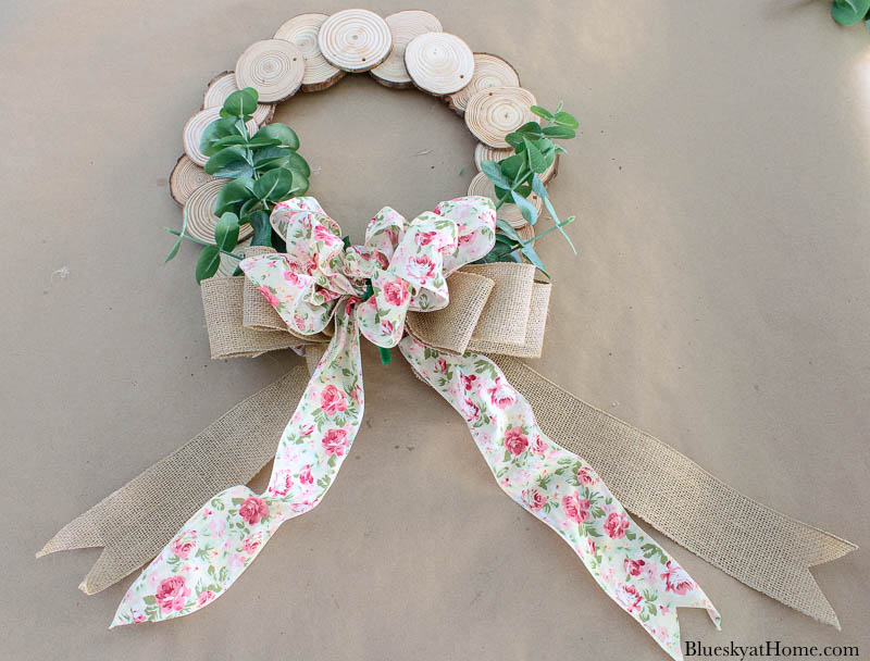 wood slice wreath with faux greenery and floral bow