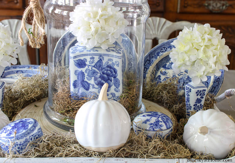 blue and white ginger ar inside cloche with white pumpkin