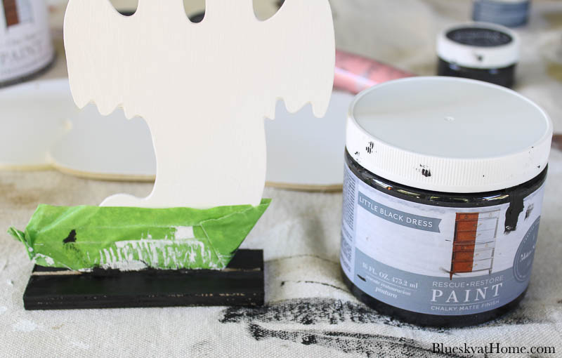can of black paint and wood ghost