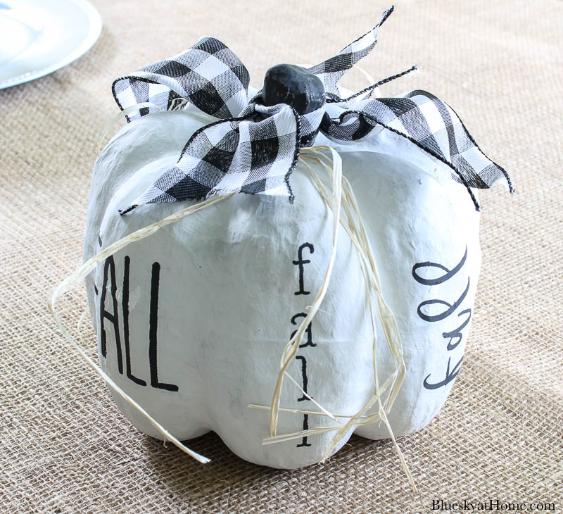 white painted pumpkin with black stencil word fall