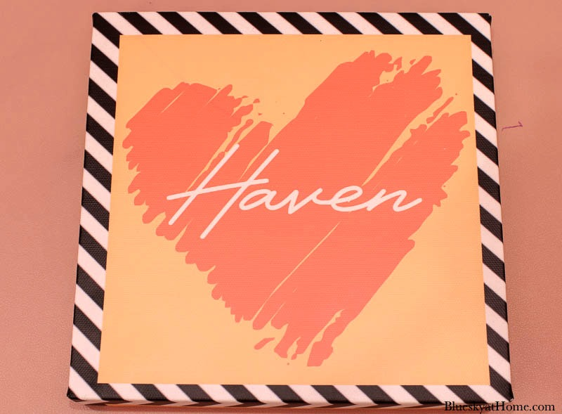pink sign with black and white stripe edge