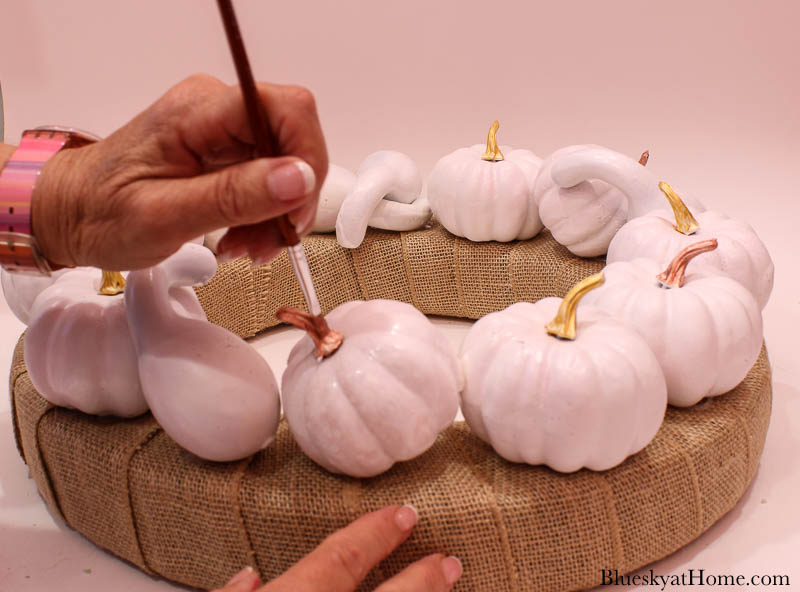 painting white pumpkins with gold metallic paint