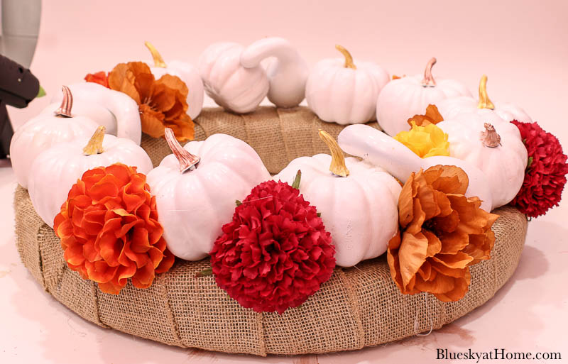 white pumpkins on burlap wreath with faux flowers