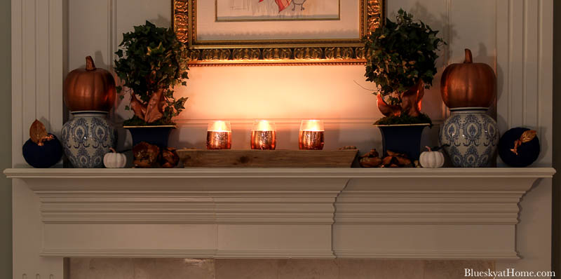 candle lit fall decorated mantel