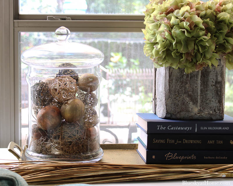 glass jar and dried hydrangeas in grain scoop on fall decorated table