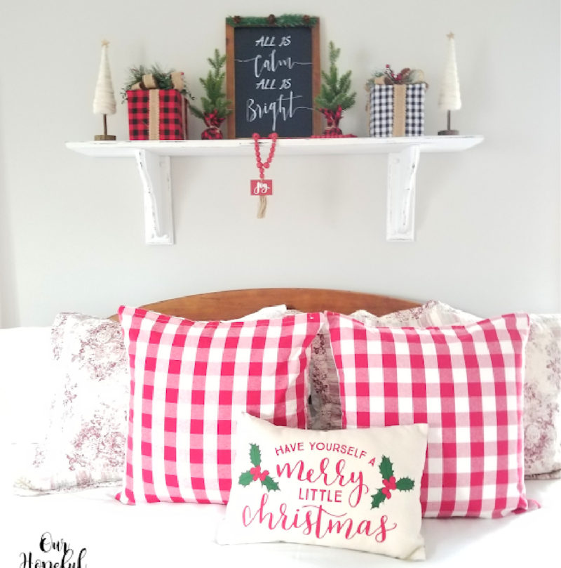 white shelf and red check pillows decorated for Christmas