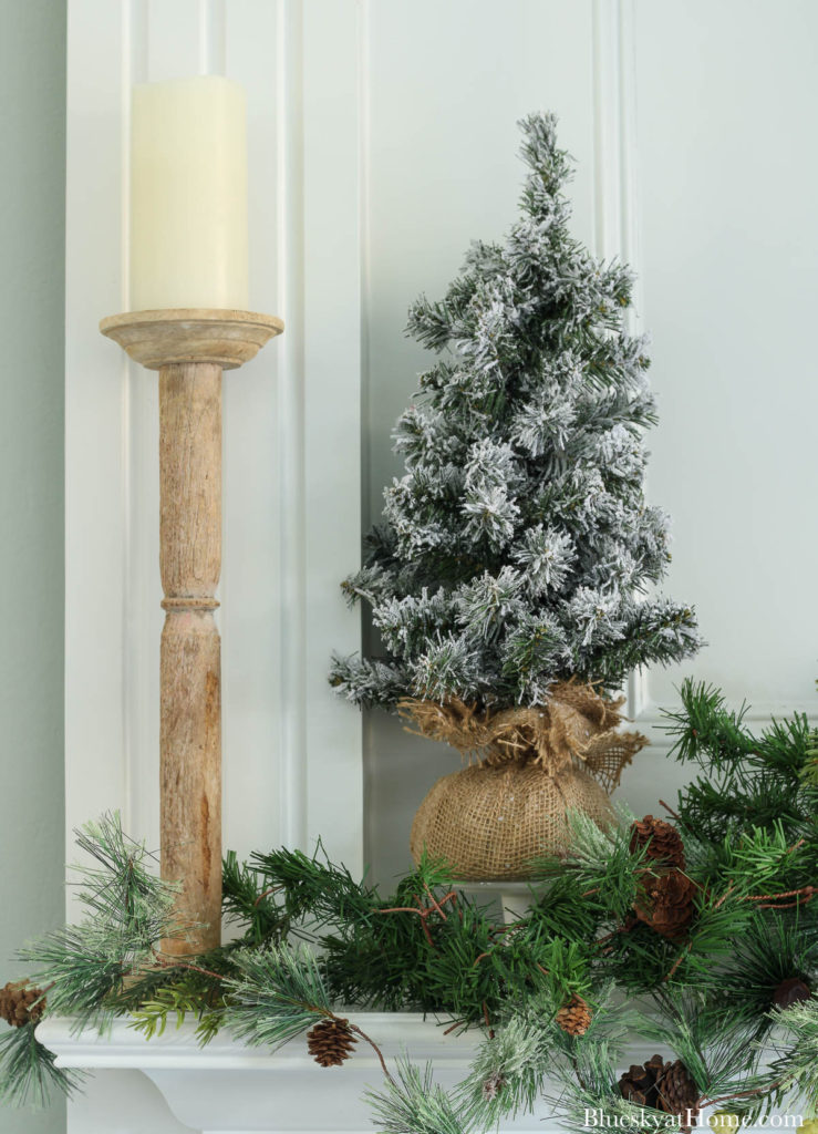 white candle with frosted tree