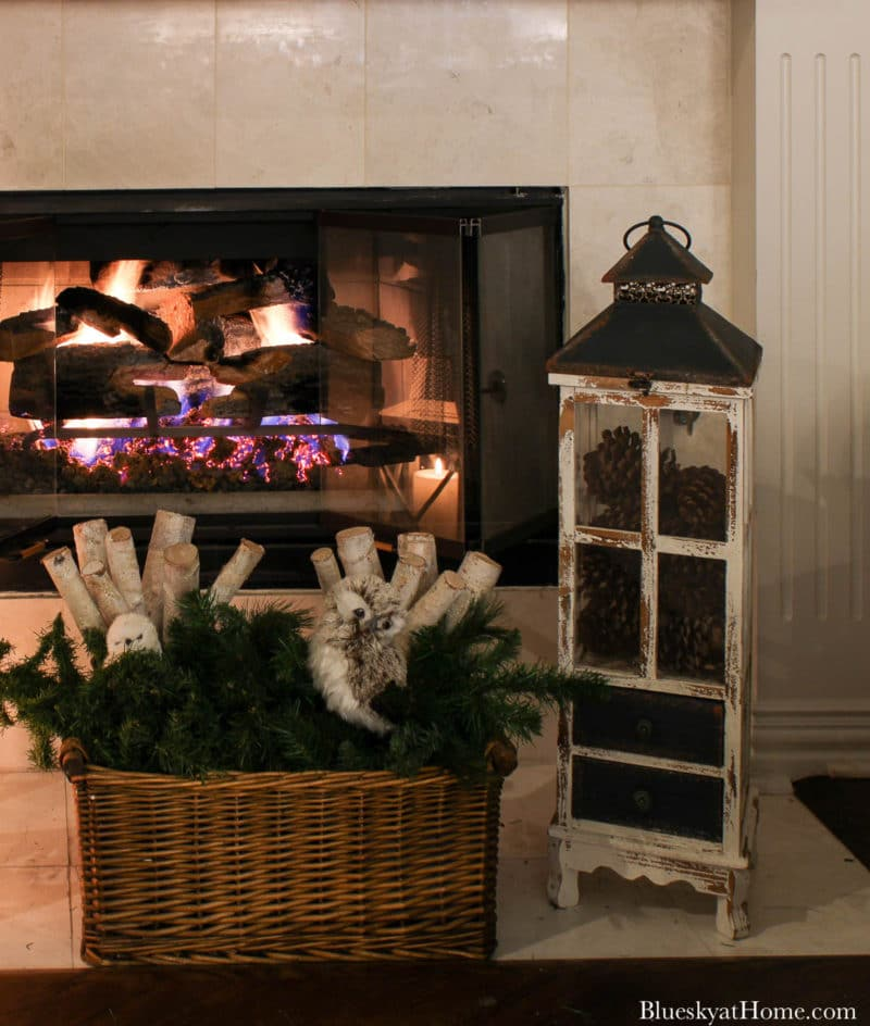 greenery and lantern in front of fireplace