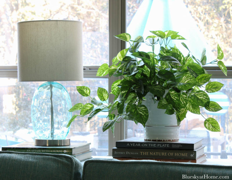 green pothos ivy in white container and aqua table on sofa table