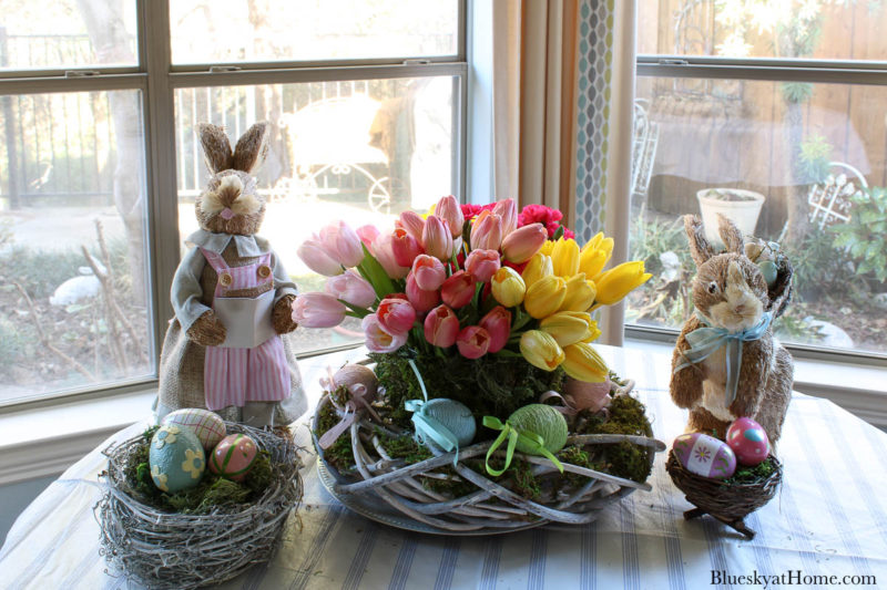 pastel spring flowers in container with bunny and eggs