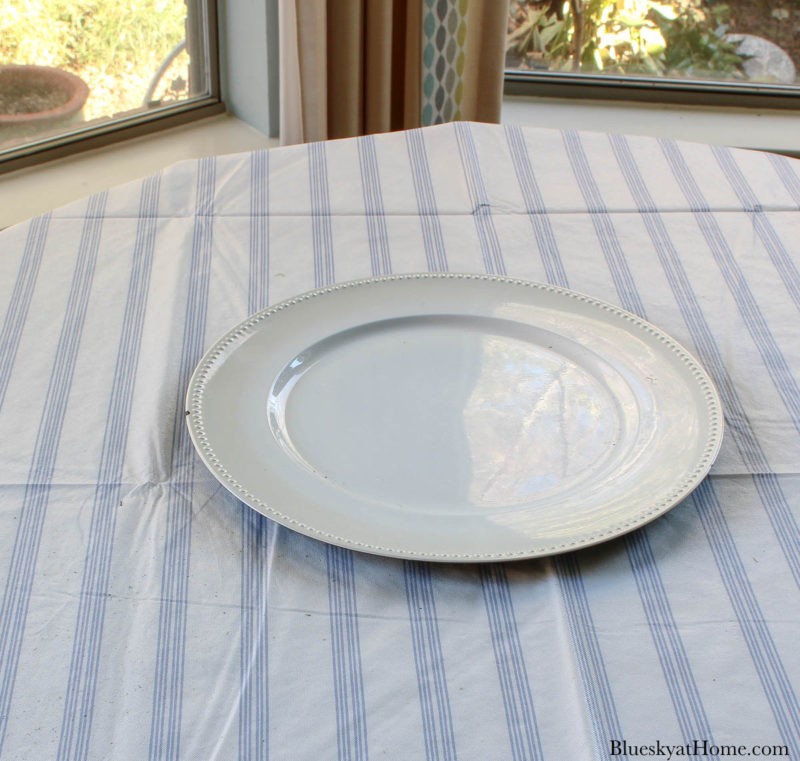 white plate on blue and white stripe tablecloth