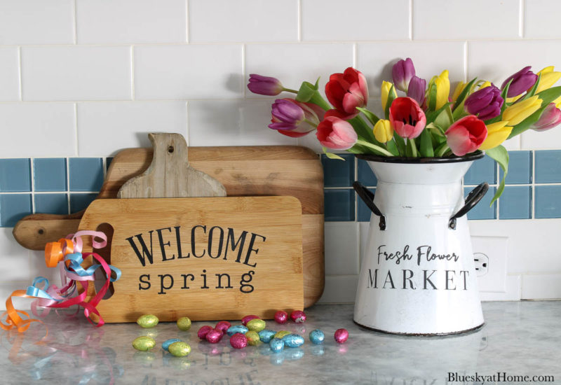 wood cutting board and container with flowers and spring home decor