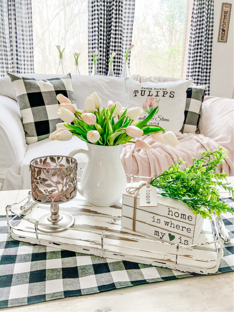 coffee table with white pitcher and pink flowers and greenery