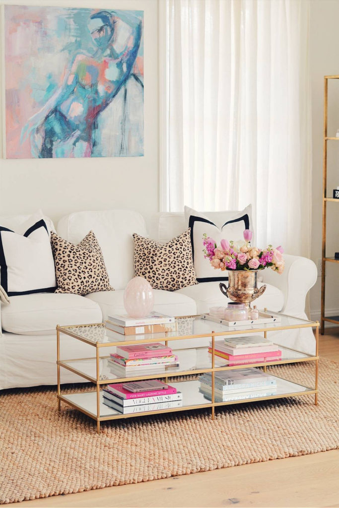 white sofa with pink accessories and pink flowers