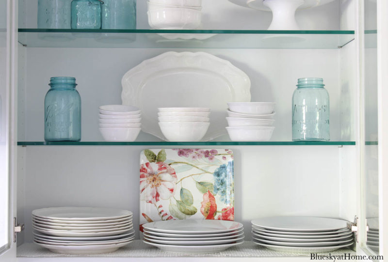 shelves with white dishes and blue mason jars for spring kitchen