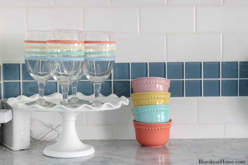 cake stand with glasses and bright pastel bowls