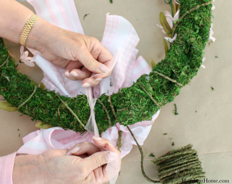 tying bow on spring floral wreath