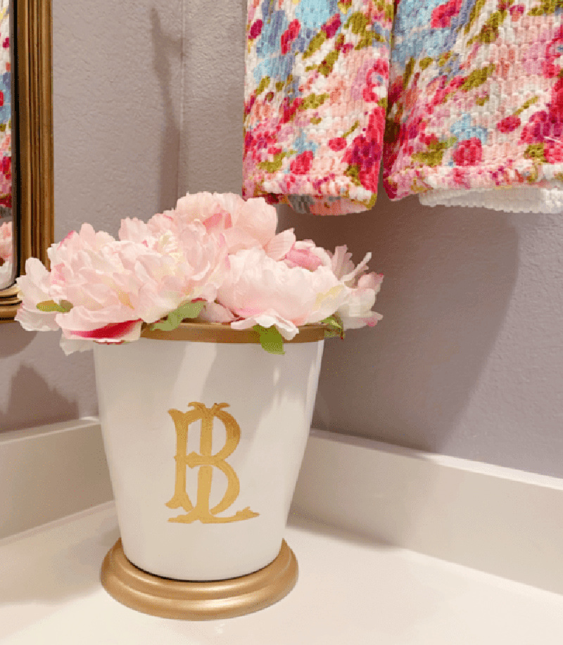 white vase with gold monogram and pink flowers