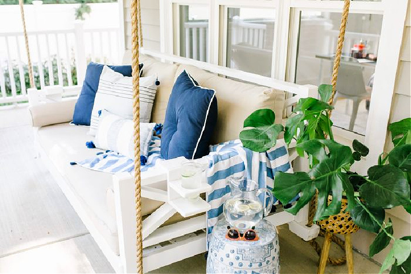 spring front porch swing with blue pillows